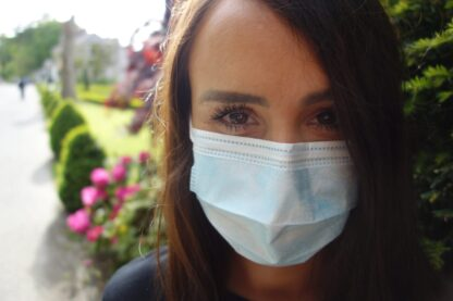 woman looking into camera with a face mask on