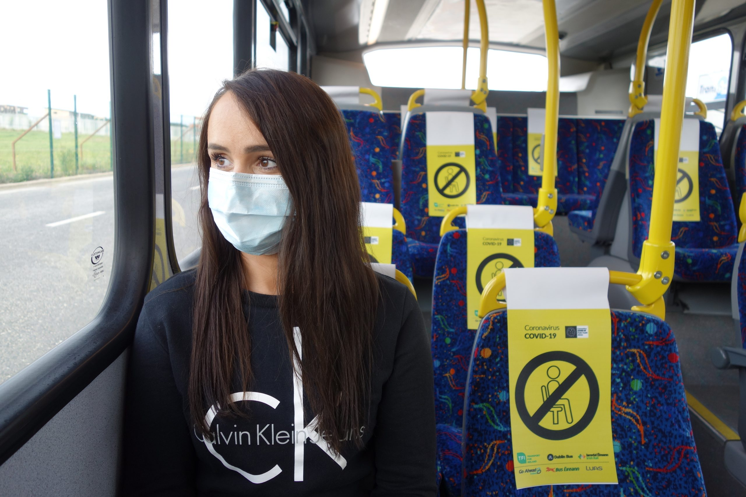 woman on a bus wearing a face mask