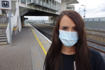 woman at train station wearing a face mask